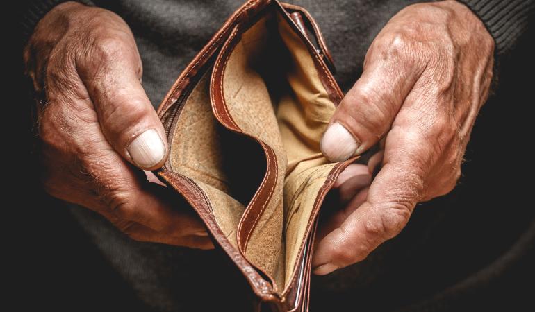 Anziano preoccupato con il portafogli vuoto